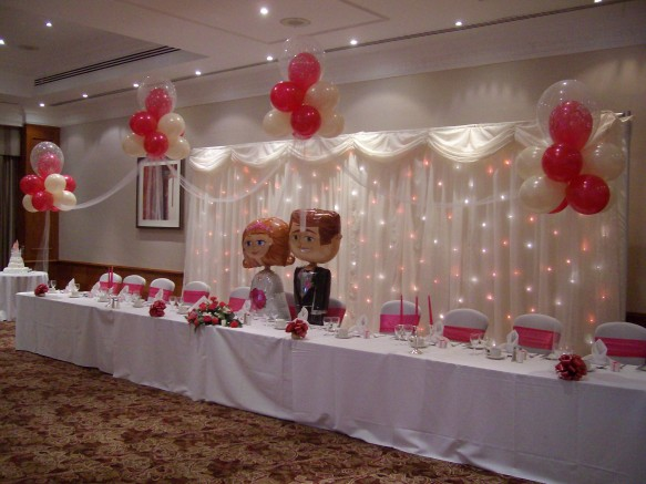 4 cloud 9s above the top table with a set of fun Bride and Groom Airwalkers. Ivory Star Cloth back drop with co-co-ordinating magenta or fushia light