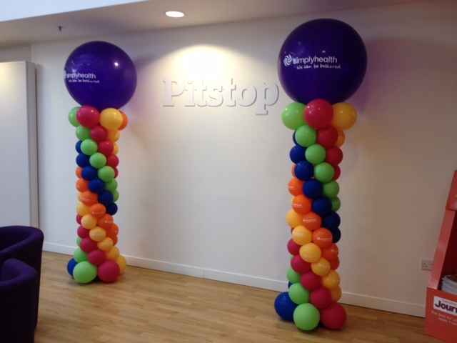 Topping off spiral columns with 3ft printed balloons sure gets the message across