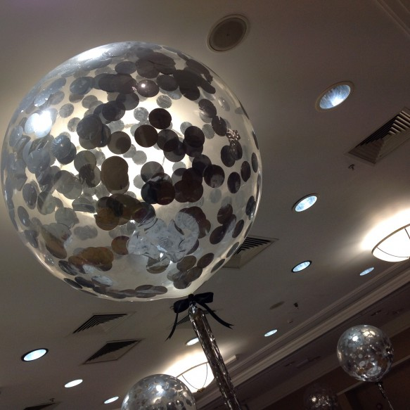 "Giant 36"" clear latex balloons with large silver confetti adorned each table"